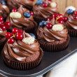 Chocolate cupcakes decorated with chocolate cream and summer ber — Stock Photo #59706963
