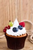 Summer cupcake decorated with cream and fresh berries  — Stock Photo