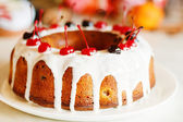Glazed bundt cake with white glaze on Christmas background — Stock Photo