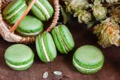 Green macaroons on dark wooden background — Stock Photo