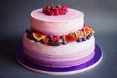 Two tiered purple cake with fruit on dark gray background — Φωτογραφία Αρχείου