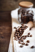 Coffee beans in wooden scoop — Stock Photo