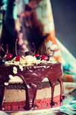 Layer cake decorated with chocolate glaze, cream flowers and che — Stock Photo