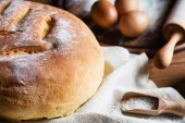 Freshly baked homemade bread with homespun fabric on rustic wood — Stock Photo