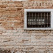 Ancient brick wall texture. Window with grill and railings. Veni — Stock Photo #65274021