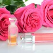 Cosmetics, perfumes, beads and three pink roses in a still life — Stockfoto #56095825