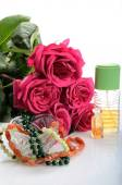 Perfumes, beads - jewelry and roses in a still life — Stockfoto