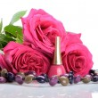 Cosmetics - nail polish, beads and three pink roses in a still life — Stockfoto #57837461