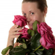 Portrait of a woman age of 35-40 years without makeup with pink roses in the hands on white background — Stock Photo #57837467