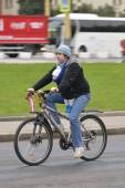 Cyclist in the city, the father who holds a small child his bosom — Stock Photo