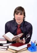 Male teacher behind a desk with book and glasses in hand — Stock Photo