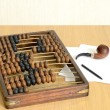 Abacus arithmetical old for accountants, sheets of paper, a pen and a pipe for of tobacco smoking in still life — Stockfoto #62481163