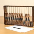 Antique wooden abacus for accountants on the table, sheets of paper and a pen in still life — Stockfoto #64070193