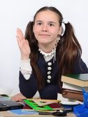 Teen schoolgirl at a school desk raises her hand to respond a lesson — Stock Photo