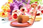 Women's cosmetics for Makeover: blush and lip gloss on a background of colorful flowers tulips — Stok fotoğraf