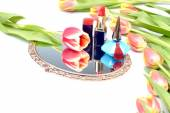 Antique gilded mirror, cosmetics for women's makeup and tulip flowers on a white background — Stock Photo