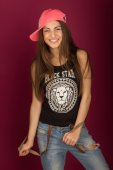Beautiful smiling brown-haired woman in a cap and jeans  — Stock Photo