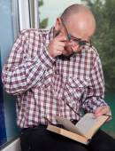 Crying nerd reading a book — Stock Photo