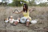 Girl with sickle and pumpkins — Stock Photo