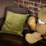 Vintage teddy bear sitting on a chair — Stock Photo #74602509