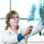 Female doctor checking xray image — Stock Photo #63710861