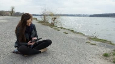 Smiling beautiful young woman sand using a tablet pc — Stockvideo