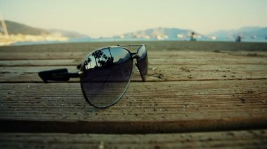 Sunglasses lying on the beach and reflect the silhouettes of people passing close — Stock Video