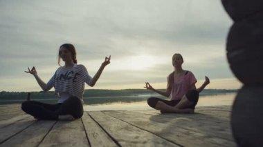 Dolly hareket: iki genç kadın yakın göl açık havada, meditasyon yoga yapıyor. Spor fitness ve doğada, sonbahar günbatımı egzersiz — Stok video