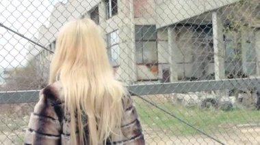 Stylish blond girl with bright makeup, in a luxurious fur coat abruptly turns around and goes into the side of the camera — Stock Video