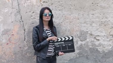 An attractive young woman holds an open film slate — Stock Video