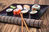 Fresh Japanese tasty sushi roll set with chopsticks on wooden ta — Stock Photo