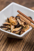 Fresh platter of mussel with chopsticks on wooden table — Stock Photo