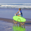 Surfer girl with a bicycle — Stock Photo #54776339