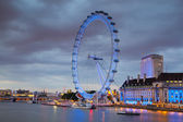 London eye in the night and south bank of river Thames, famous London's walk and tourist destination — Stockfoto
