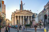 LONDON, UK - DECEMBER 19, 2014: Royal Exchange building in sun set and square with lots of office people passing the Bank street. — Stock Photo