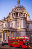 LONDON, UK - DECEMBER 19, 2014: City of London. St. Paul cathedral in dusk and red british double bus on the bus stop. People walking by the cathedral — Stock Photo