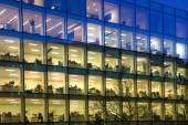 LONDON, UK - DECEMBER 19, 2014: Office block with lots of lit up windows and late office workers inside. City of London business aria in dusk. — Stock Photo
