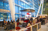 LONDON, UK -  MARCH 28, 2015: Heathrow airport Terminal 5. Cafe and people waiting for arrivals — Stock Photo