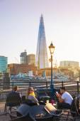 LONDON, UK - APRIL15, 2015: Little cafe and tourists in front of Shard of glass, the tallest building in Europe. South bank of river Thames walk. — Stok fotoğraf