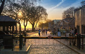 LONDON, UK - APRIL15, 2015: Tower park in sun set. River Thames side walk with people resting by the water — Stok fotoğraf
