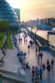LONDON, UK - APRIL15, 2015: South walk of river Thames in sun set light. View includes a lot of walking people and London hall building — Stok fotoğraf