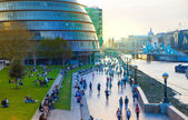 LONDON, UK - APRIL15, 2015: South walk of river Thames in sun set light. View includes a lot of walking people and London hall building — Stockfoto