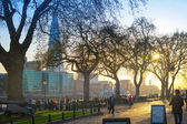 LONDON, UK - APRIL 15, 2015: Tower park in sun set. River Thames side walk with people resting by the water — Stockfoto