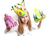 Little girl demonstrating her craft works Easter bonnet, paper dolls and reindeer — Stock Photo