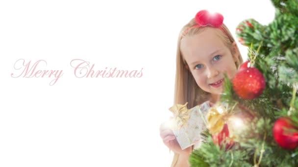 Niña con regalo sonriendo detrás del árbol de Navidad de Navidad — Vídeo de stock