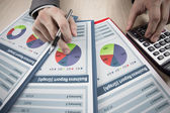 Businessmen analysing a bar graph using a manual calculator — Stock Photo