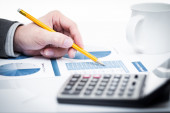 Financial adviser is reviewing report with charts and graphs — Stock Photo