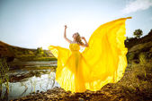 The beautiful girl with long hair in the yellow fluttering dress — Stock Photo