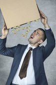 Businessman leaking money out of the box — Stock Photo