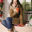 Happy young girl at home decorated on Christmas, bringing gifts to friends — Stockfoto
